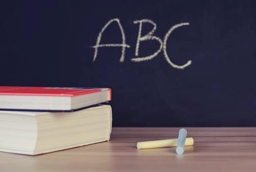 Tableau noir derrière une table, sur la table se trouvent deux manuels et de la craie.