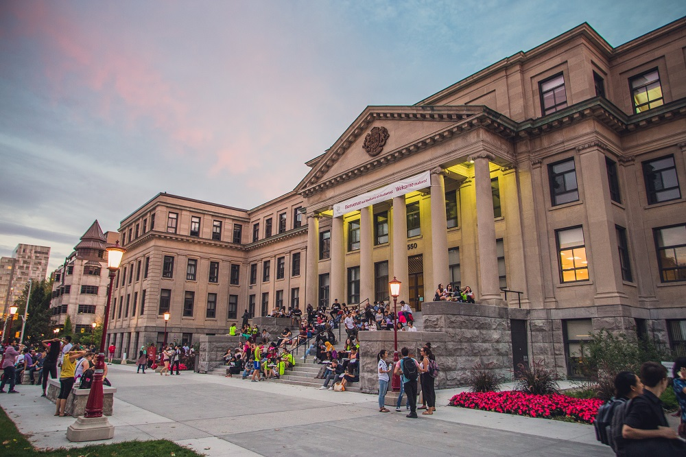 Tabaret Hall at sunset, with students sitting on the front stairs