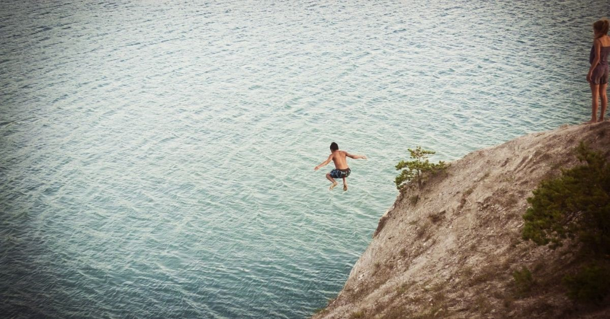 Man jumping off a cliff into a body of water