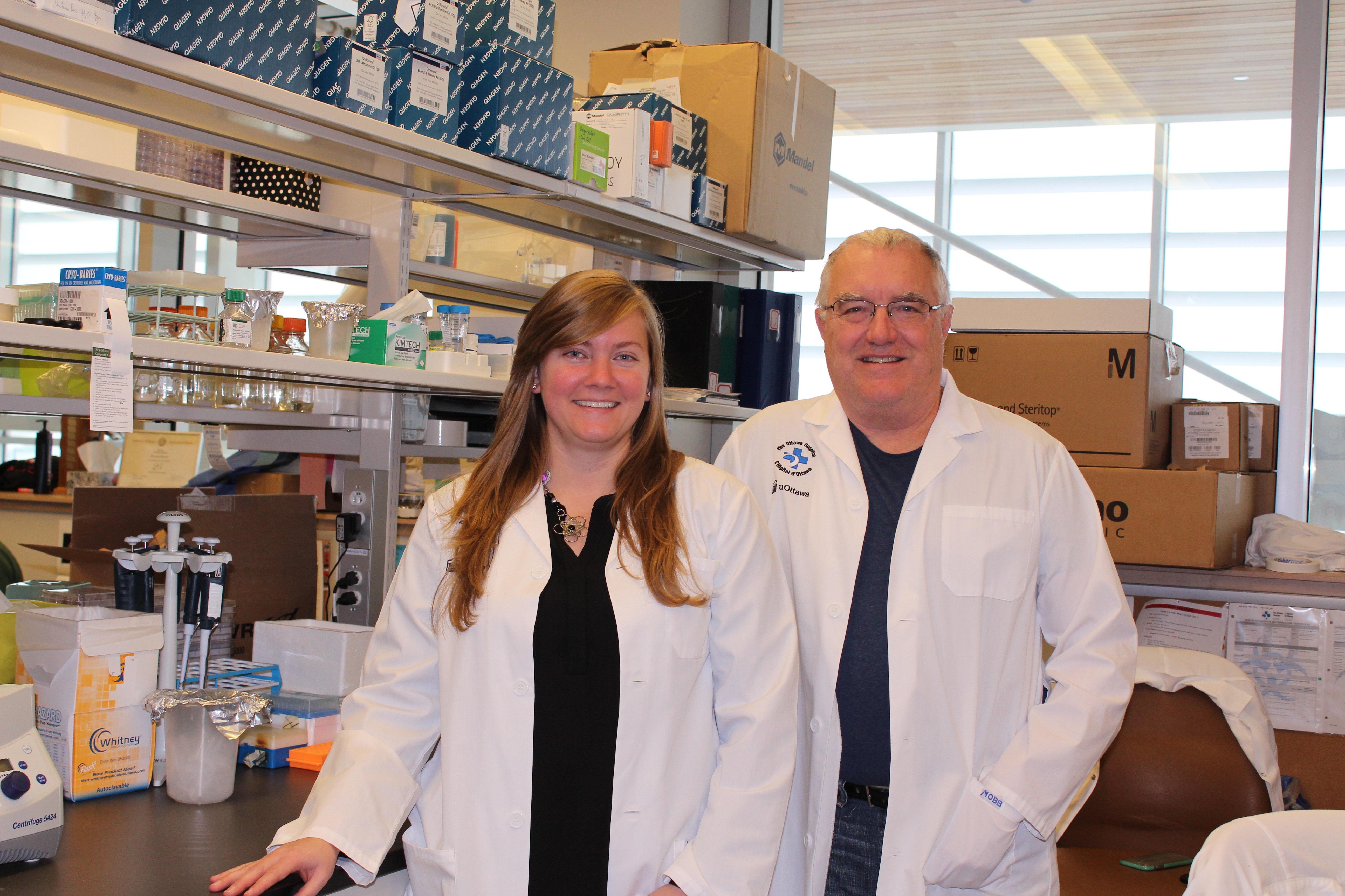 Une femme et un homme, en sarraus, sont debout dans un laboratoire de recherche.