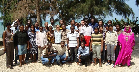 Yves Bourgault with about 30 students in a class photo taken on a beach in Senegal.