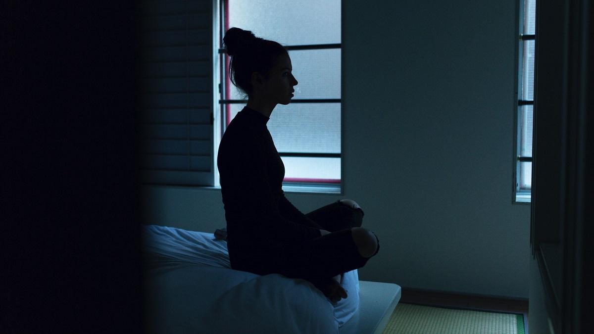 Une femme assise sur son lit dans l'obscurité