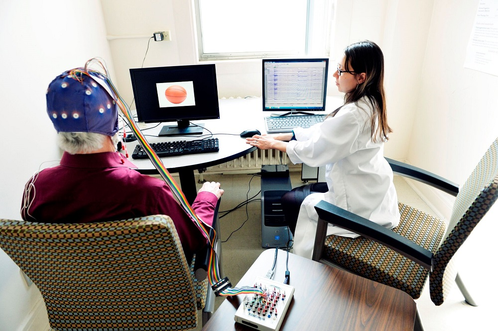 Doctor and patient wearing helmet of sensors in front of a computer screen