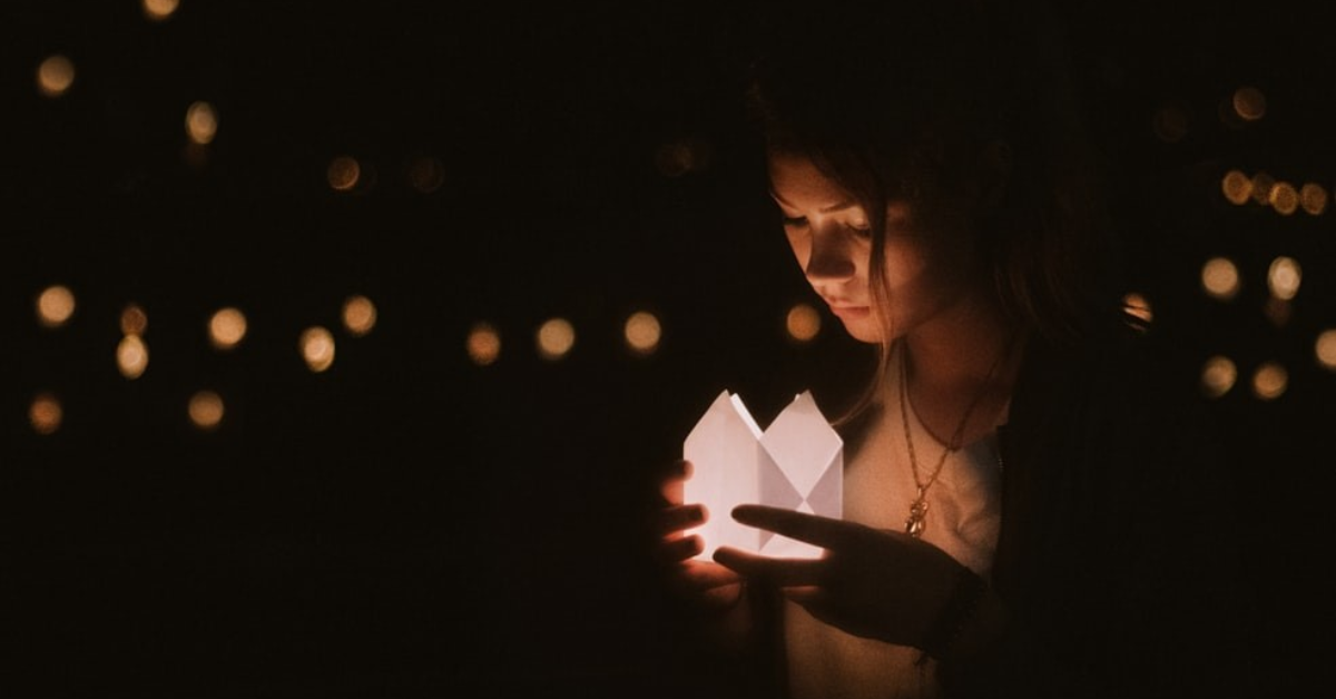 Woman holding candle during a commemorative ceremony.