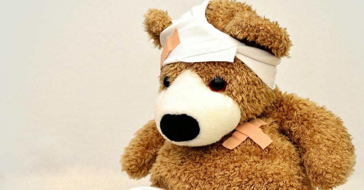 Un ourson en peluche avec un pansement sur la tête et sur le coeur