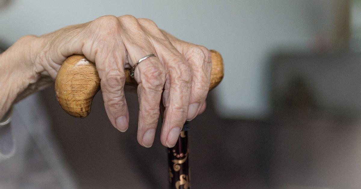 An elderly woman's hand on a cane