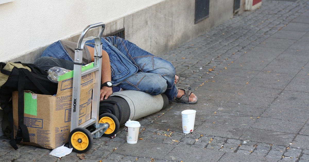 A person lying on the ground with personal belongings around