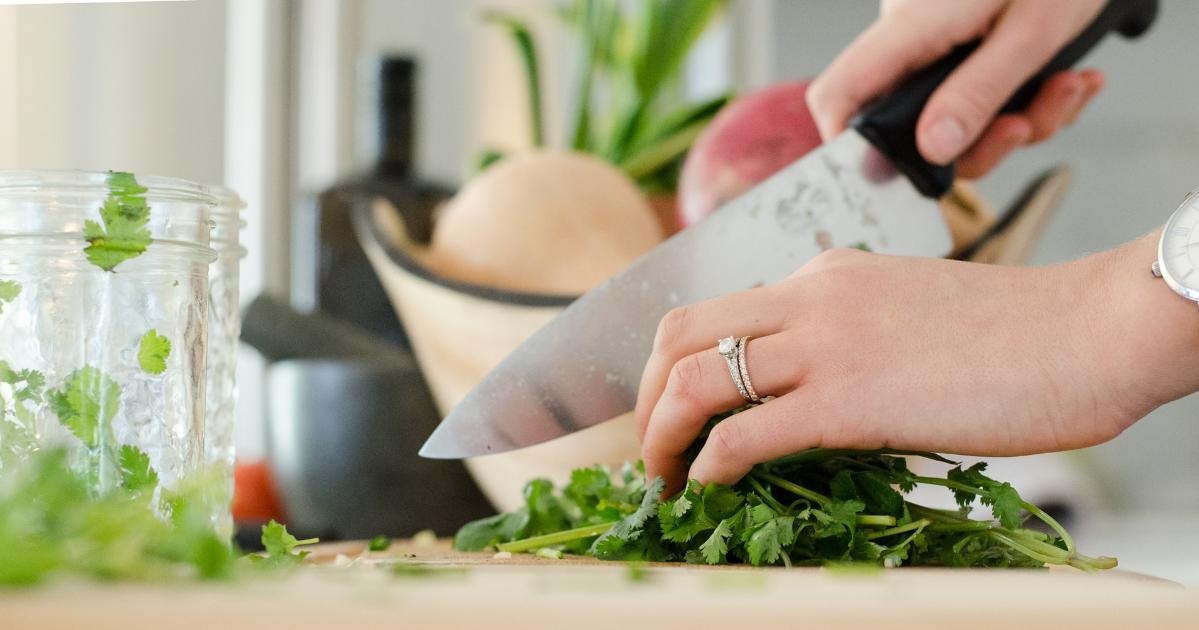 Une personne qui coupe un aliment vert