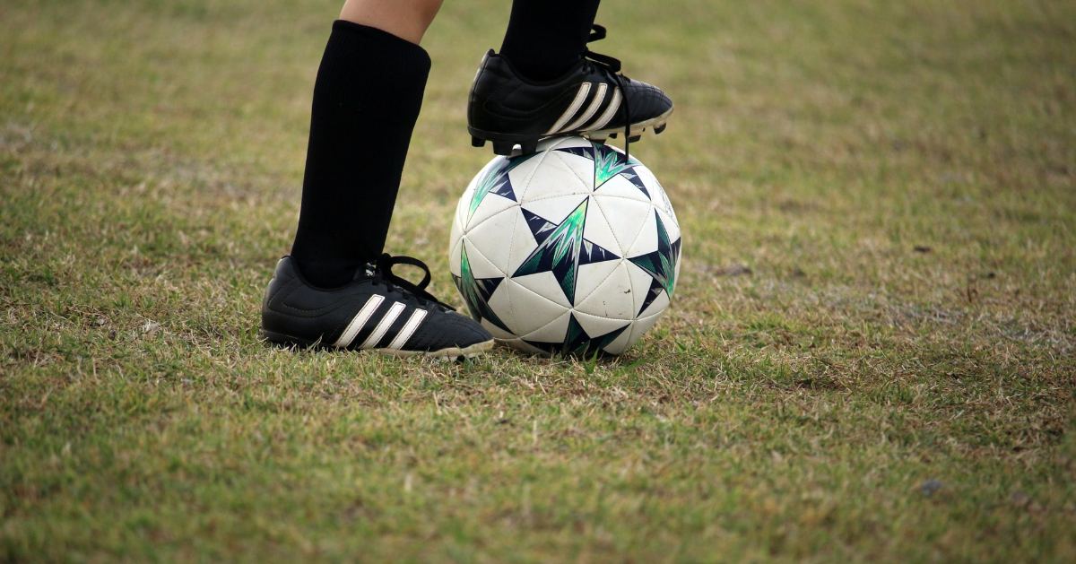 Kid with a foot on a soccer ball