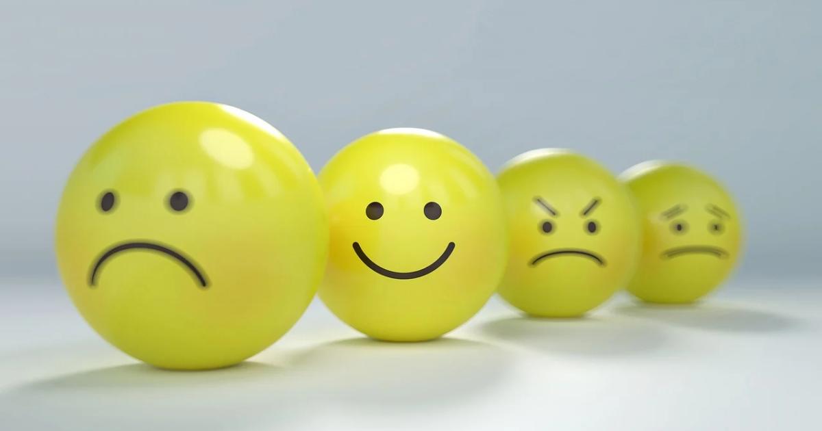 Une balle jaune avec un visage triste, un visage souriant et un visage fâché