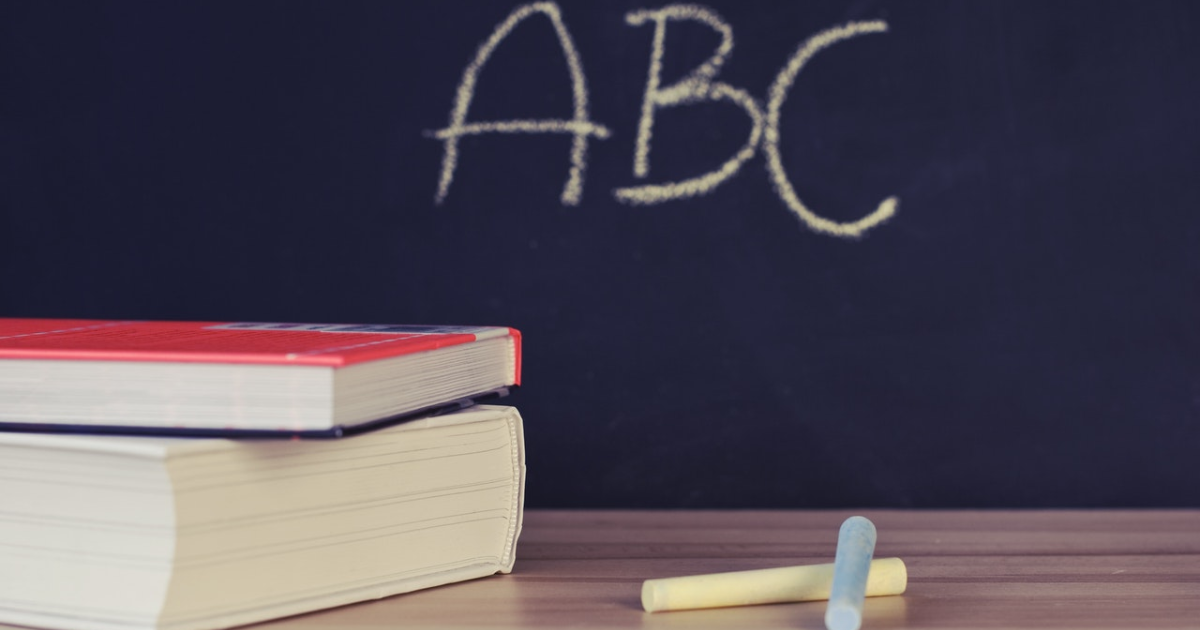 ABC written on a classroom board, chalks and books