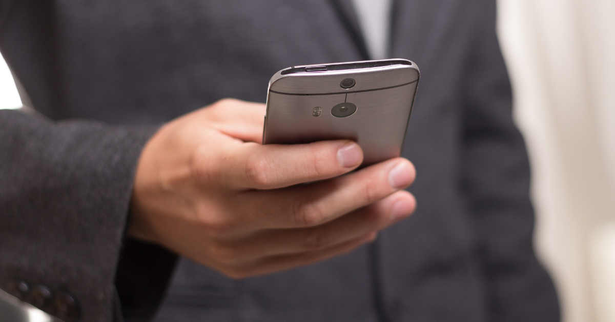 A young person holding a smartphone.