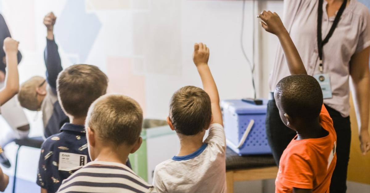 Jeunes élèves posant des questions en classe.