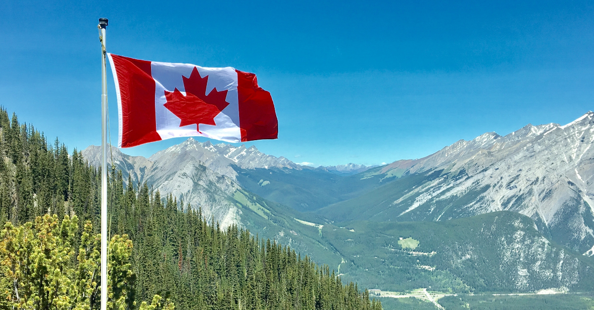 Canada flag in front of mountains.