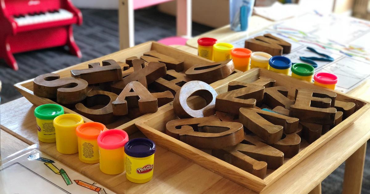 Une table avec des lettres, des crayons, de la pâte à modeler et autres activités pour enfants