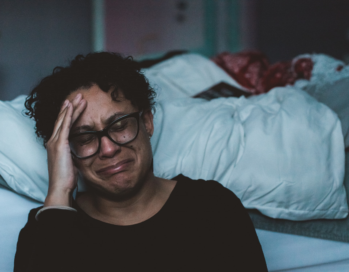 Middle-aged Black woman at foot of bed crying