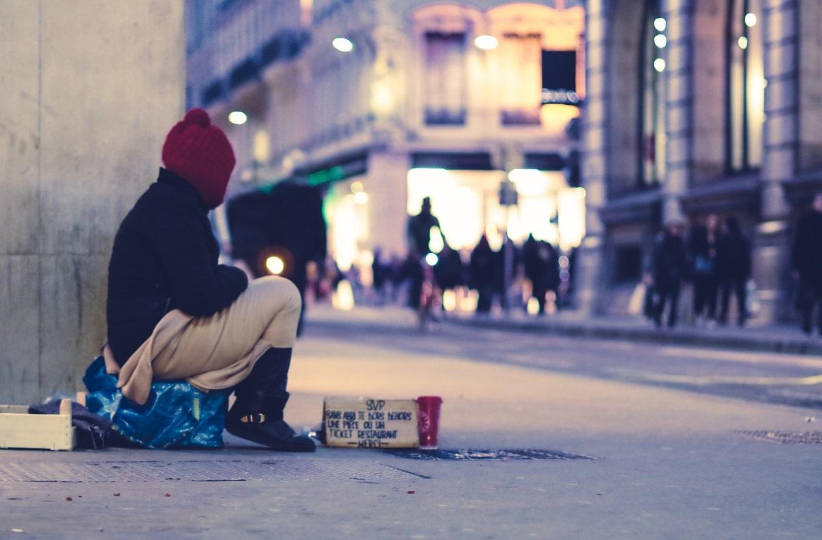 Personne dans la rue avec une pancarte demandant de l'argent