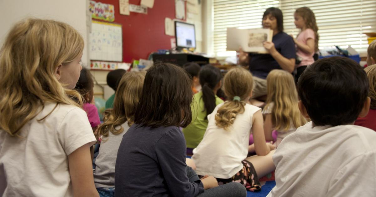 Une enseignante lit un livre à des enfants dans une classe