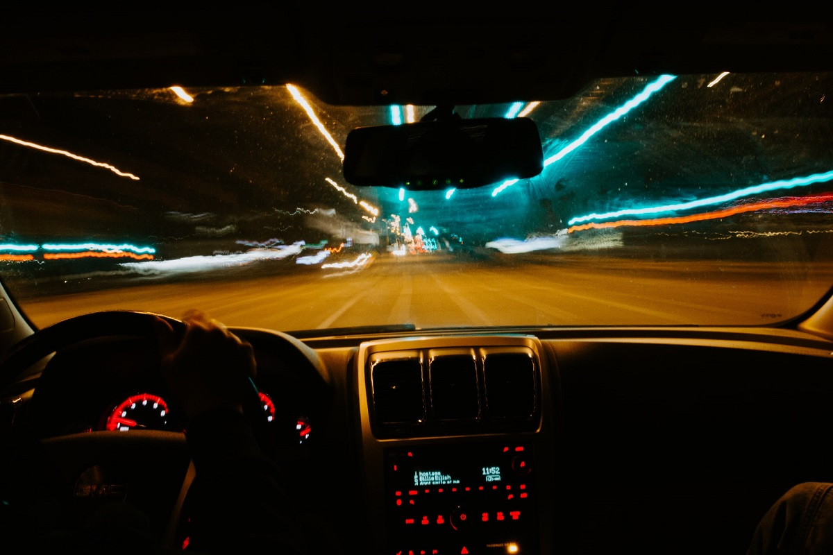 View of blurry streets at night from standpoint of the car's driver