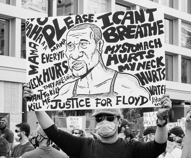 Un manifestant tient une pancarte à l'effigie de George Floyd