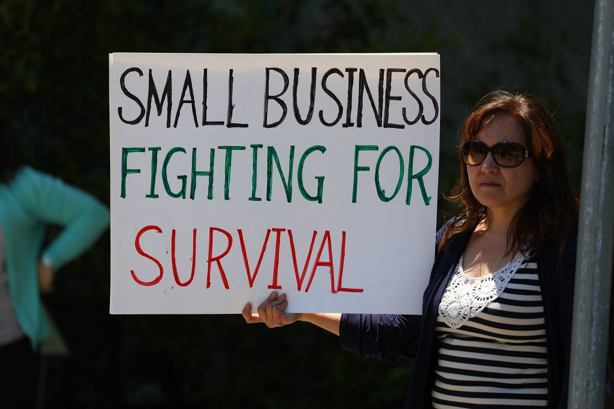 Woman holding sign that reads 'Small business fighting for survival'