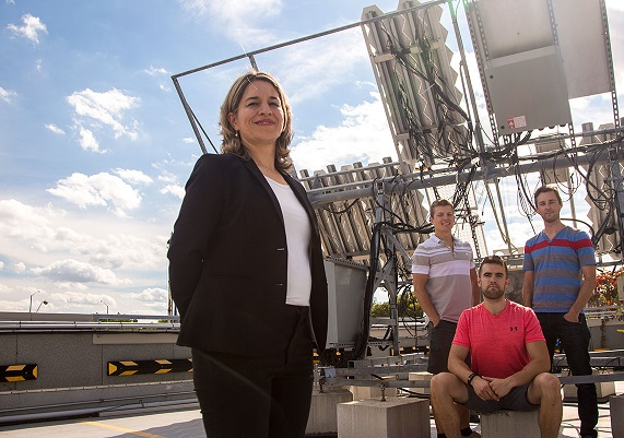 Karin Hinzer, uOttawa Professor standing with her team in front of high tech solar equipement