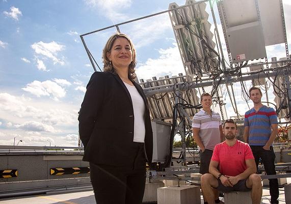 Karin Hinzer, uOttawa Professor standing with her team in front of high tech solar equipement