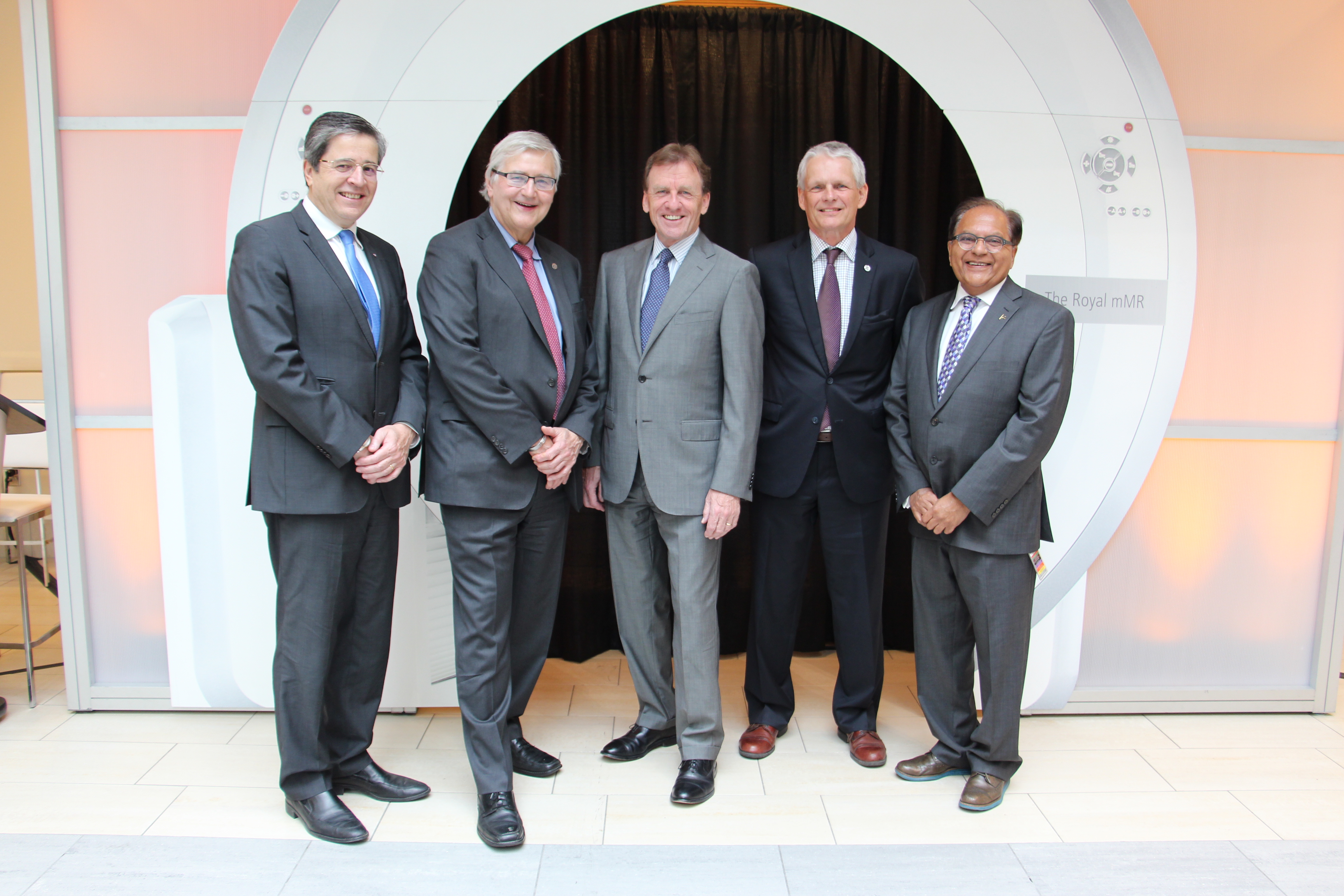 Dignitaries stand together in front of a MRI machine backdrop.