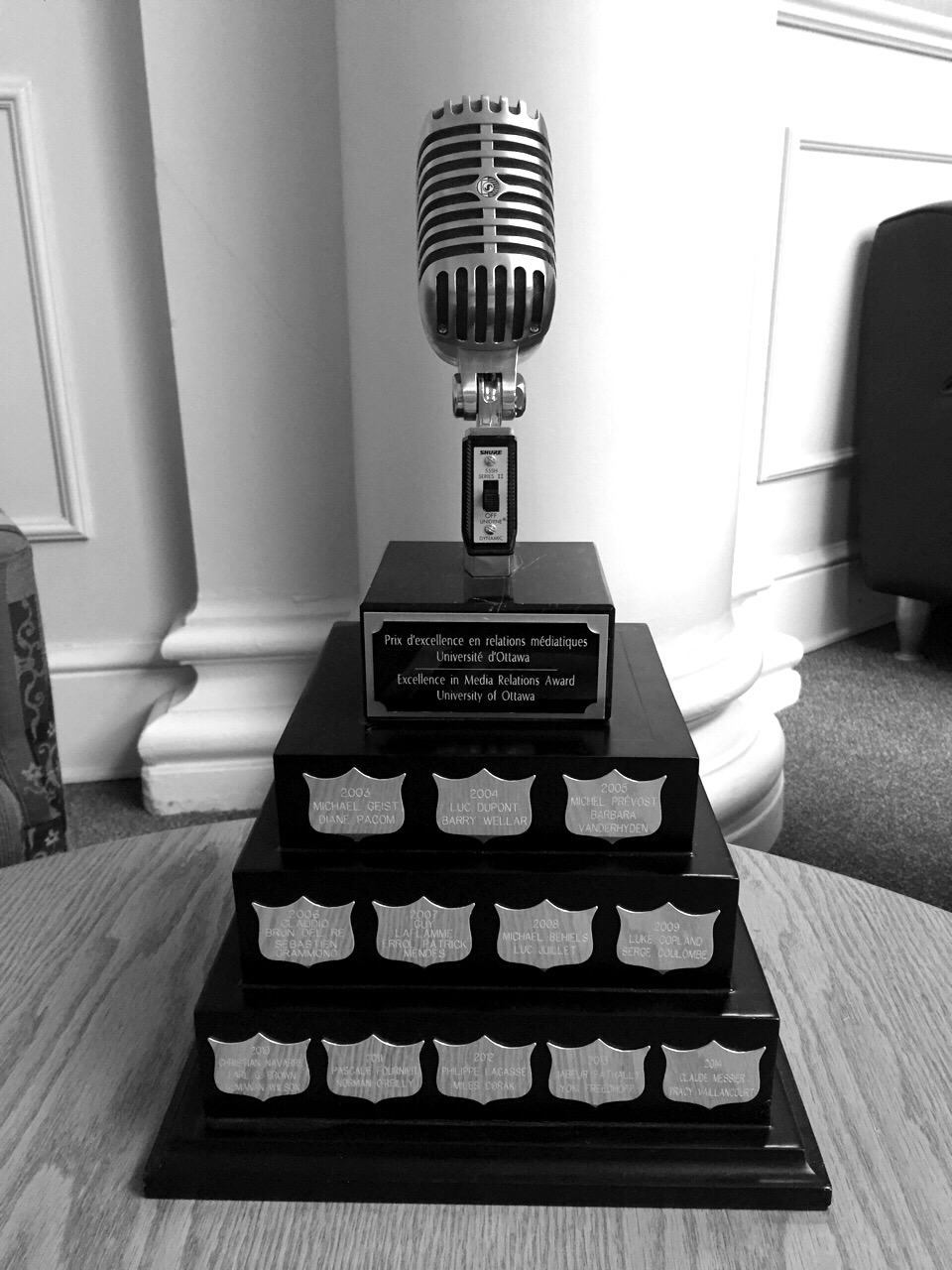 Large trophy with a microphone at the top sitting on a table.