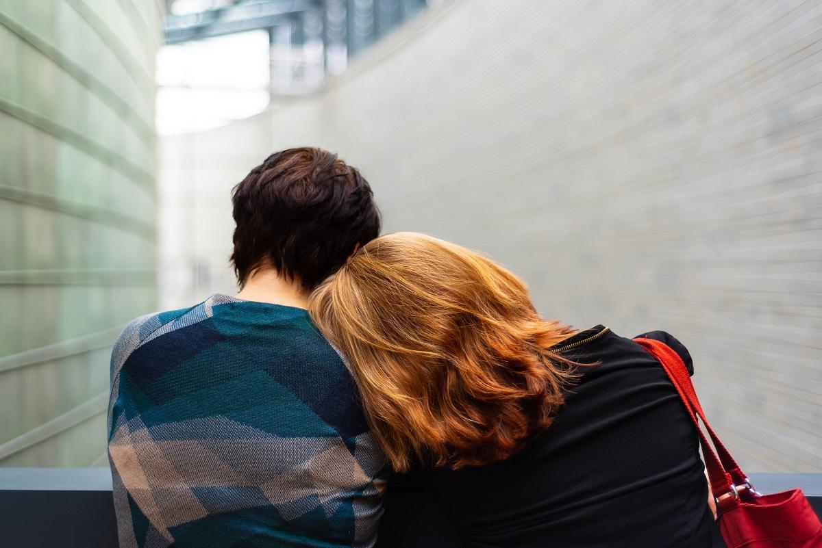 Une mère appuie la tête sur l'épaule de son adolescent