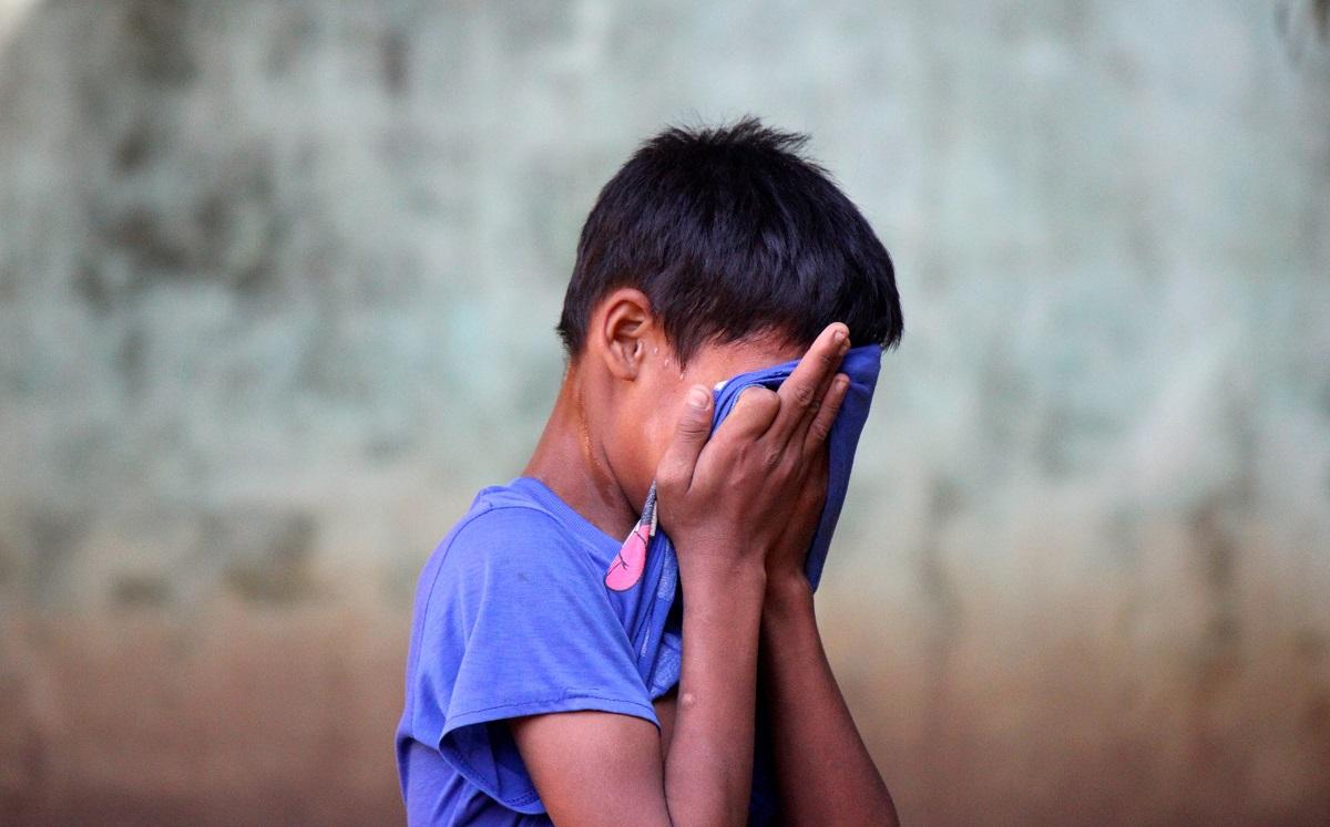 Jeune garçon Rohingya avec la tête dans les mains