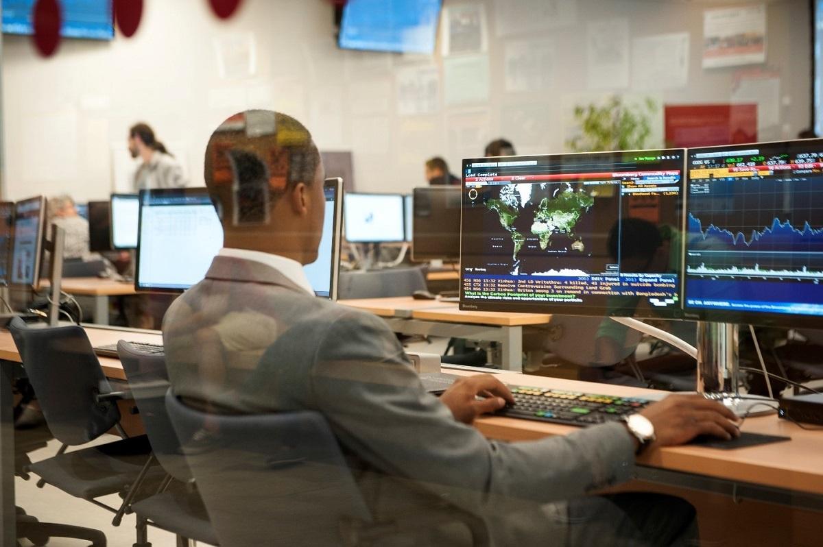 Profil arrière d'un homme en costume à un bureau utilisant un ordinateur