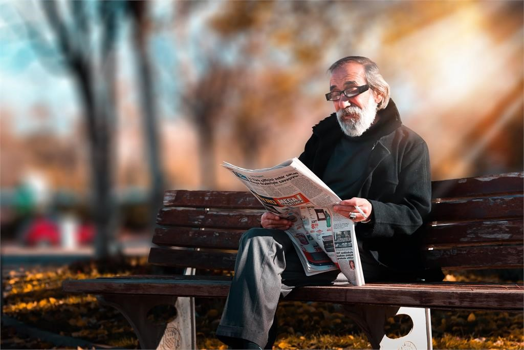 Older man sitting on a bench reading a newspaper