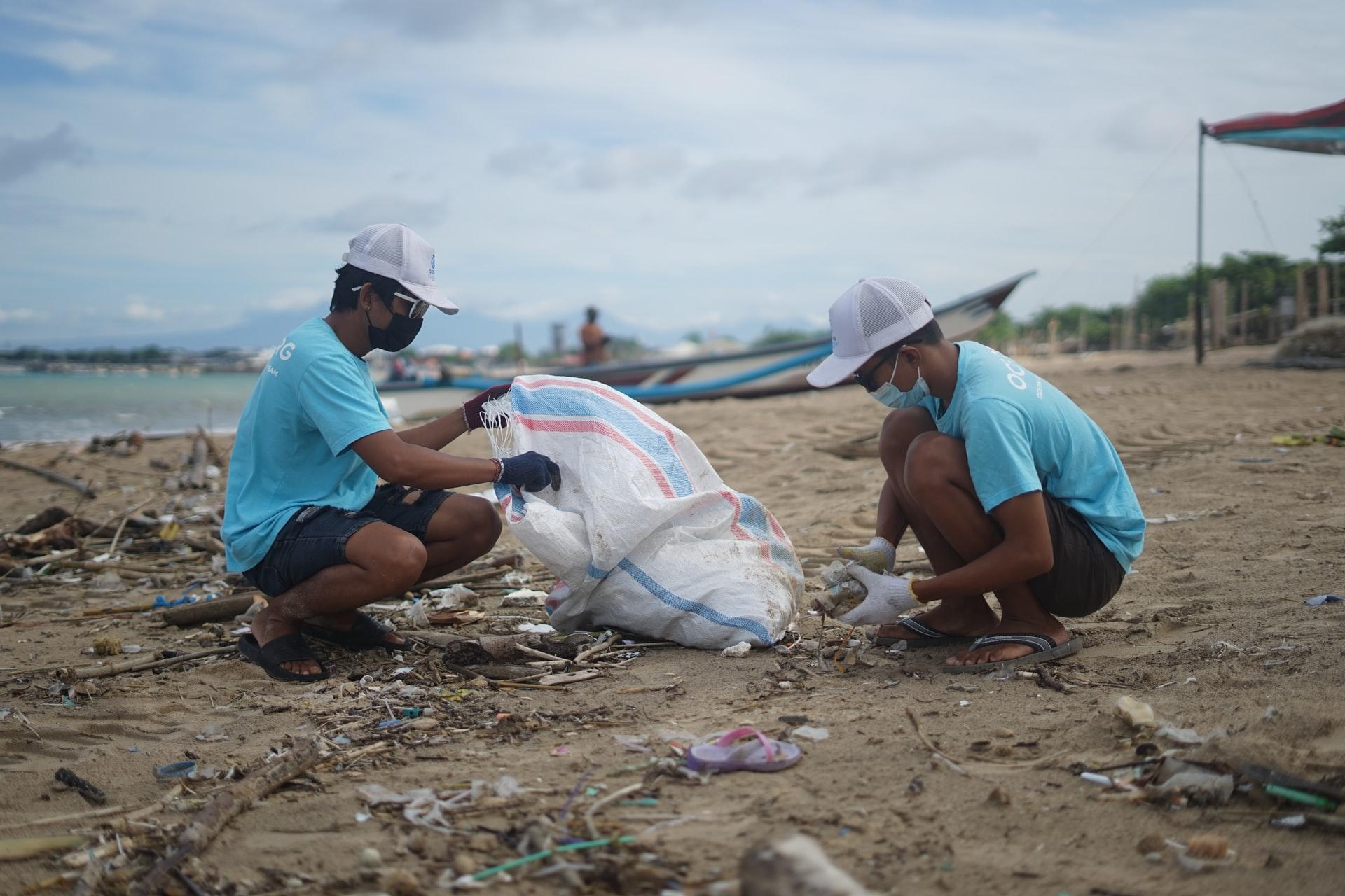 Deux travailleurs ramassent des déchets d'une plage
