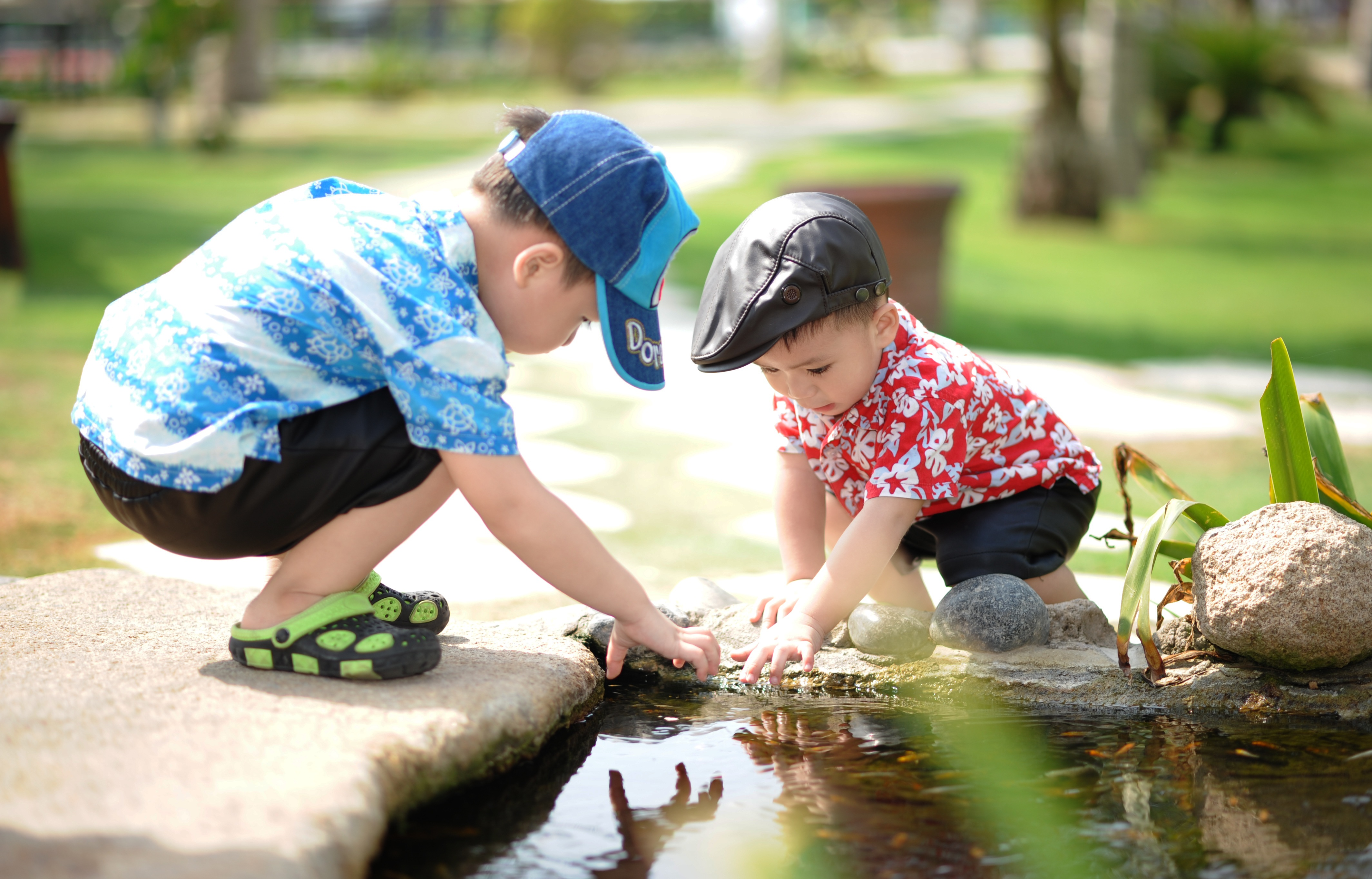 Two young children playing near a fountain