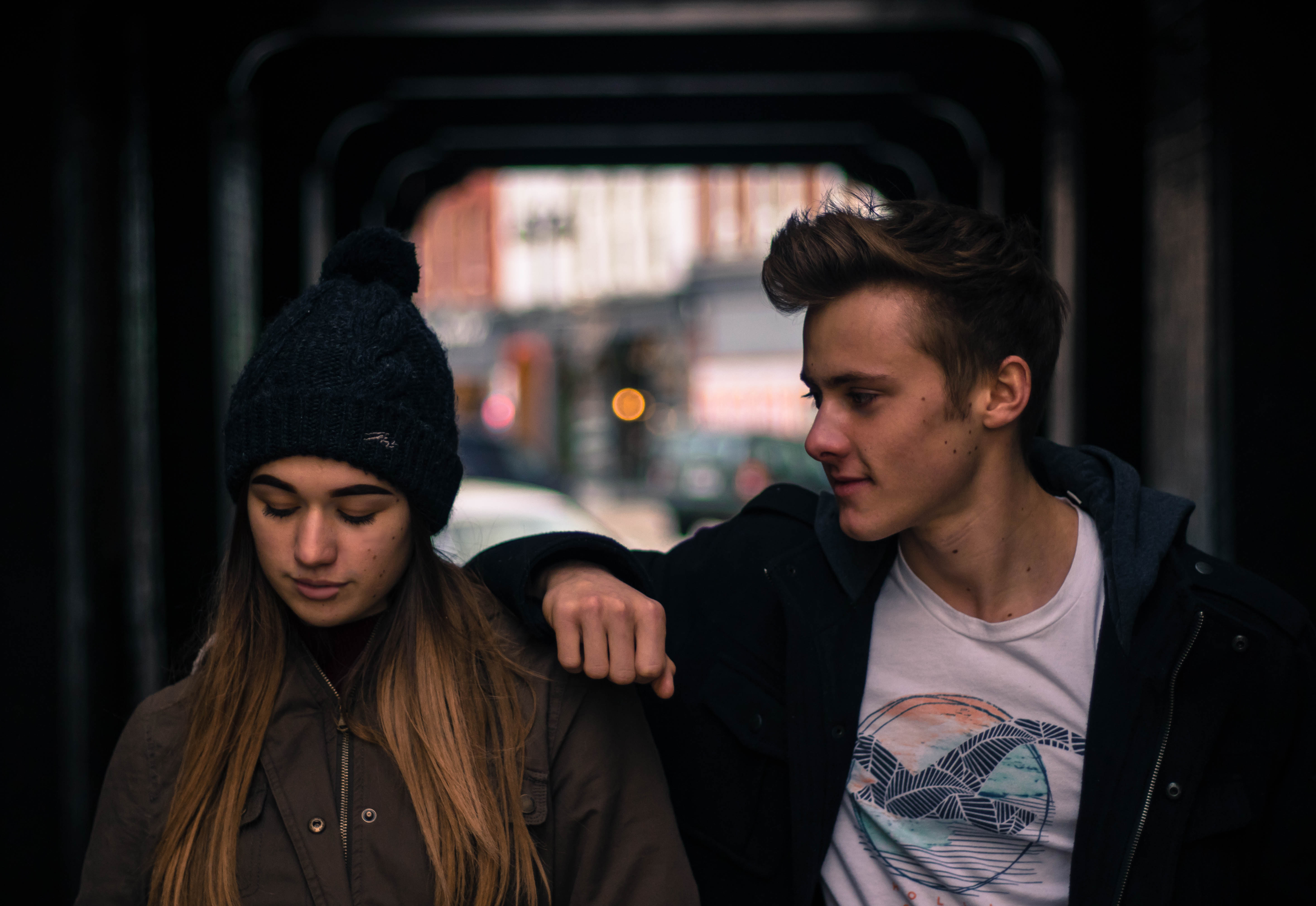 Young man and young woman talking in the street in an underpass