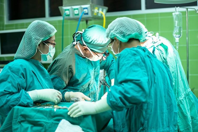 Quatre urgentologues en tenue chirurgicale turquoise se penchant sur une table d'opération