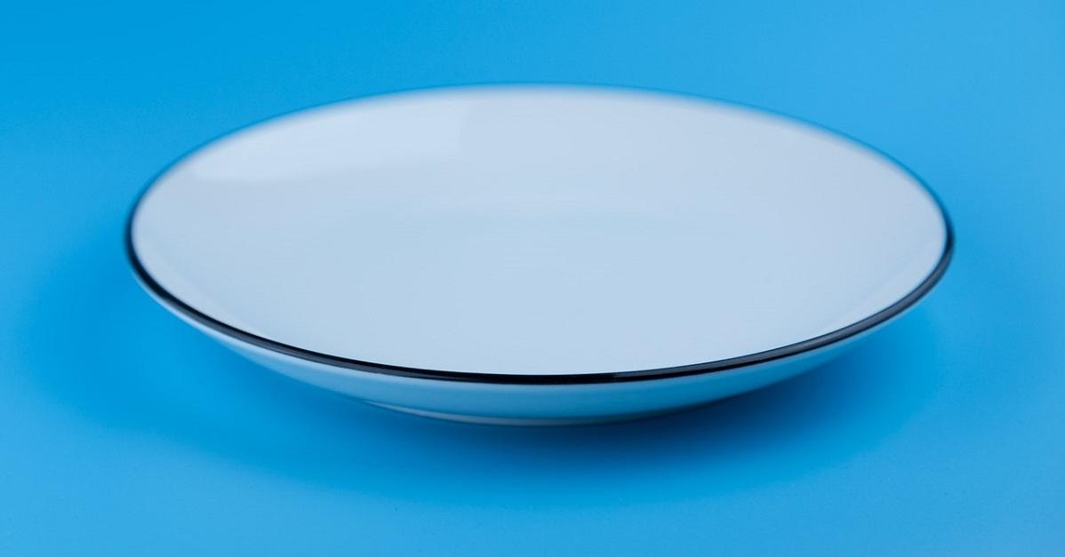 Assiette vide sur fond bleu pâle