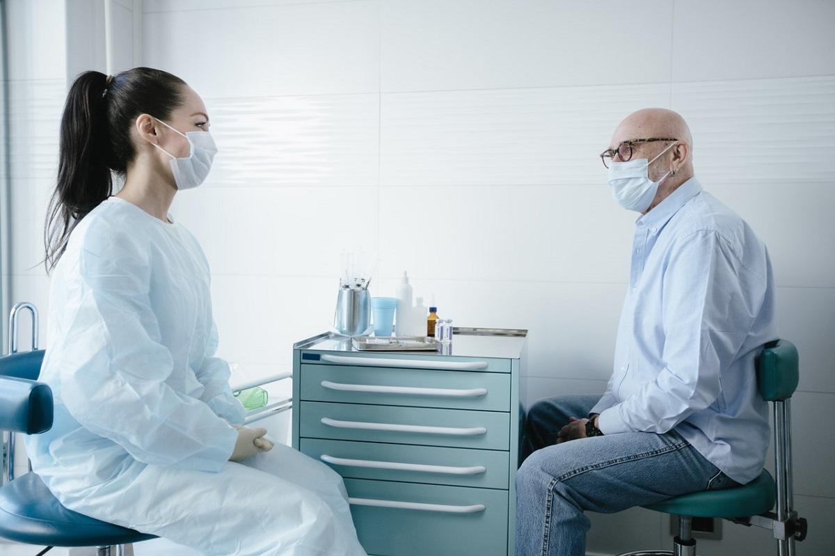 Un médecin parle avec un patient, tous deux portant des masques