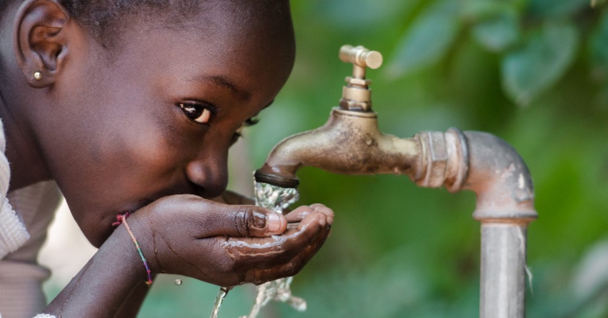 A child drinking water out of a faucet