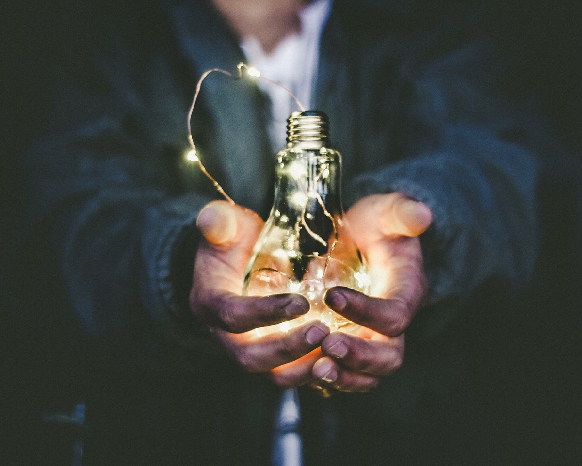 Coal stained hands holding glowing lightbulb