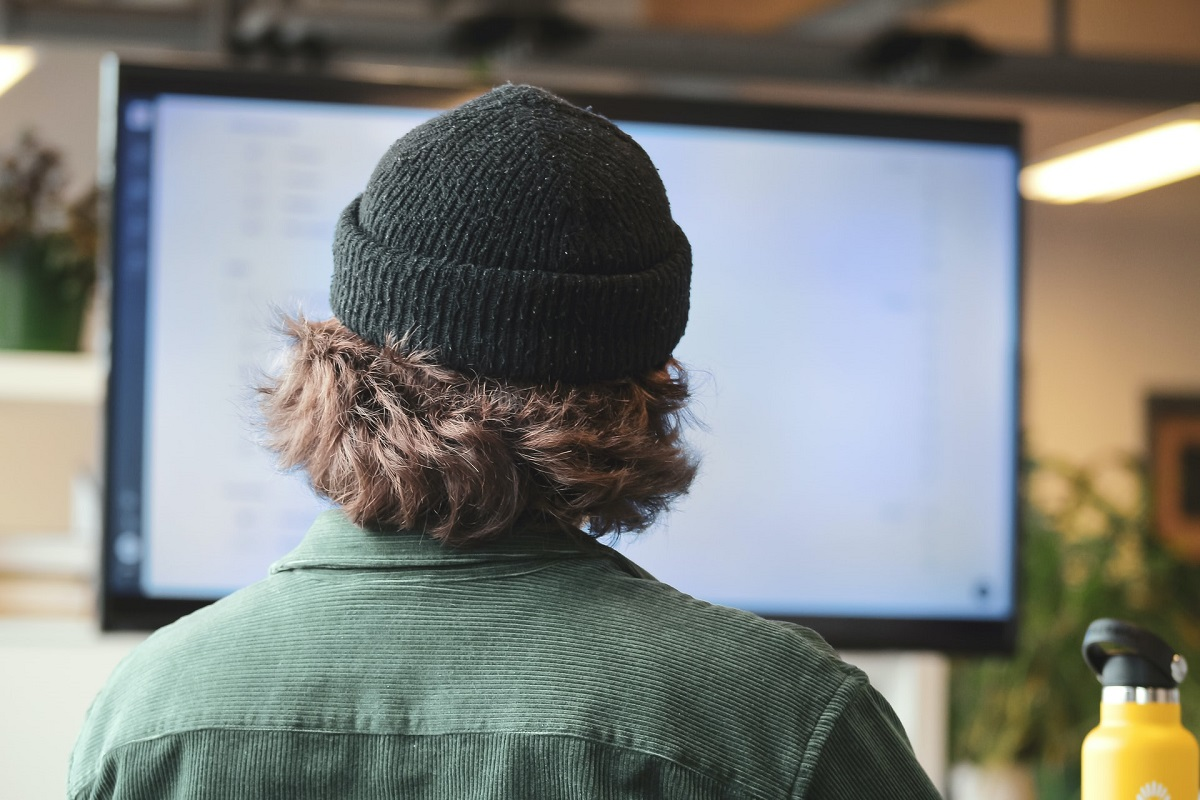 Vue de dos d'un homme en toque regardant un écran d'ordinateur
