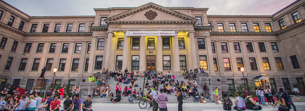 Tabaret Hall at sunset with groups of students in front of the building.