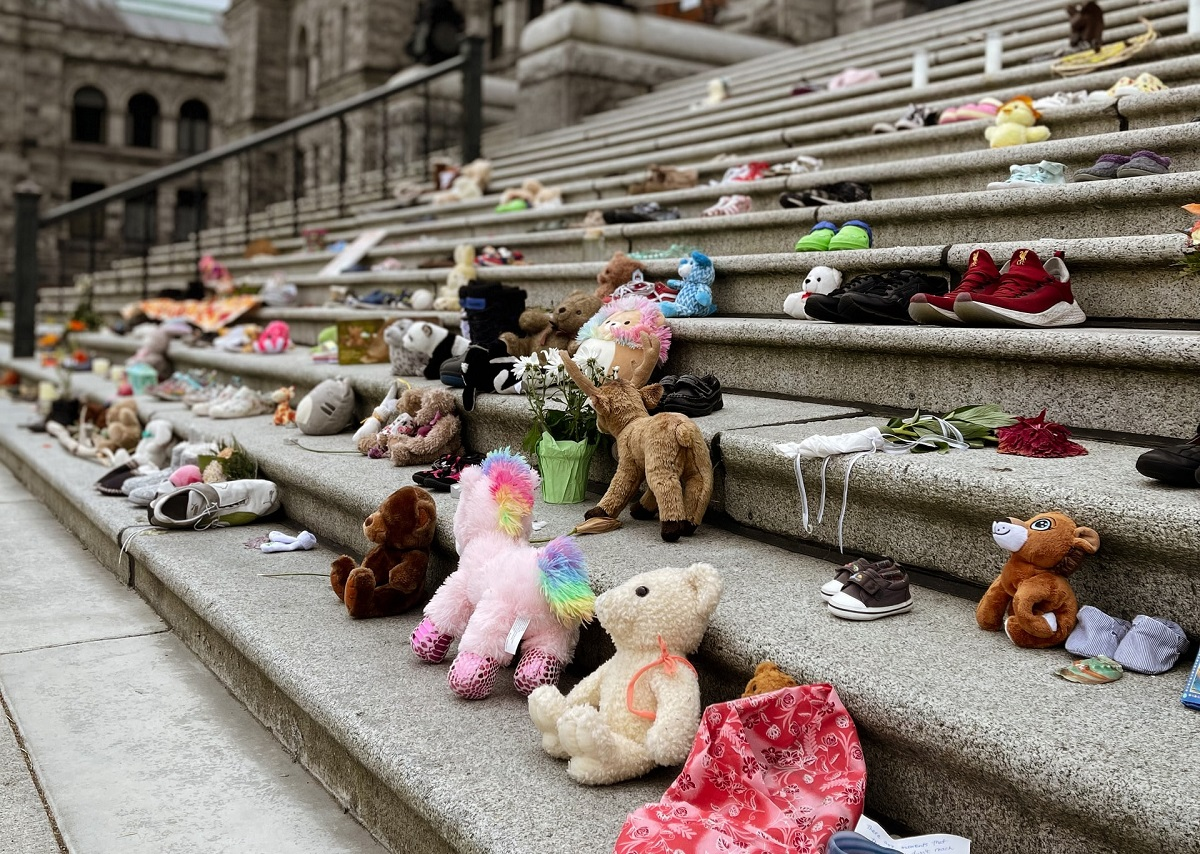 Children's shoes, dolls on steps to symbolize Truth and Reconciliation