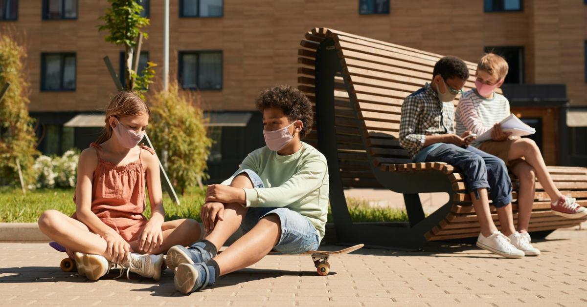 Kids outside of school, wearing masks