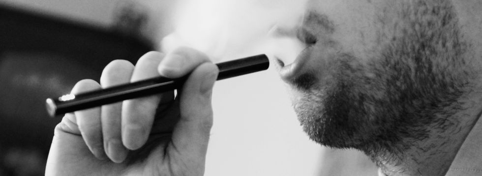 Man inhales vapour from an e-cigarette.