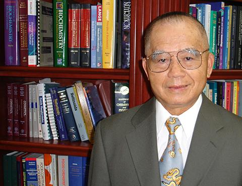 Photo de Dr Yu devant une bibliothèque
